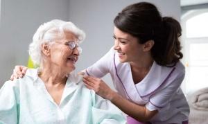 Junge Altenpflegerin lächelt Seniorin zu und legt die Hände auf ihre Schultern.